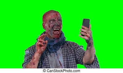 Man in zombie makeup makes selfie phone isolated over green...
