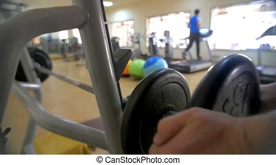 Man increasing weight on barbell