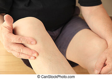 Man indicates painful area on his knee