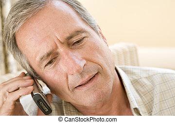 Man indoors using cellular phone