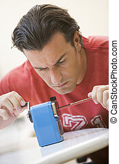 Man indoors using pencil sharpener
