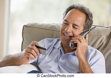 Man indoors using telephone and looking at credit card smiling