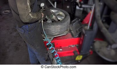 man inflate tire air on mounting machine. Mechanic using air...