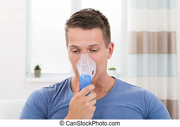 Man Inhaling Through Inhaler Mask