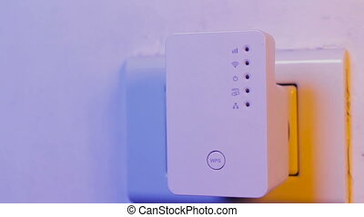 Man insert ethernet cable into WiFi extender device which is...