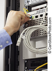 Man inserting USB wire in data server in data center