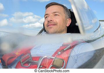 man inside the cockpit flying in glider