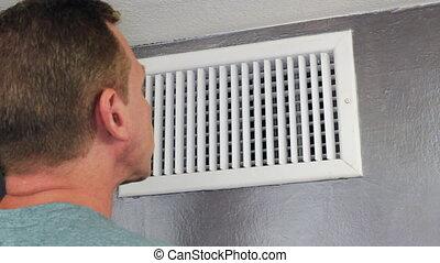 Man Inspecting an Air Vent - Mature male looking inside an...