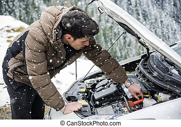 Man inspecting car engine in the snow