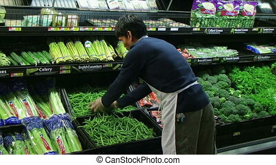Man Inspecting Green Beans In Produce