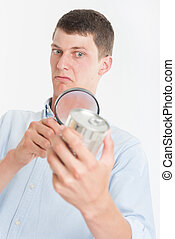 Man inspecting nutrition label - Young man inspecting a cans...