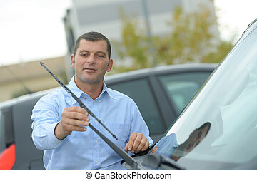 man inspecting the cars wipers