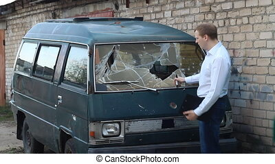 man inspects a broken car minibus, insurance, police
