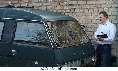 man inspects a broken car minibus, insurance