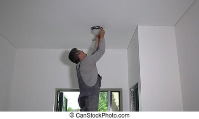 Man install led light lamp into ceiling hole. Static shot.