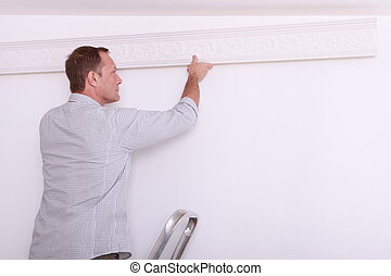 man installing a protection on a wall