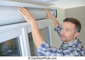 man installing cassette roller blinds on windows