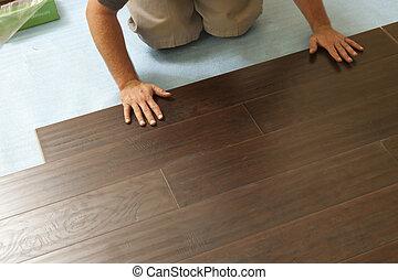 Man Installing New Laminate Wood Flooring Abstract.