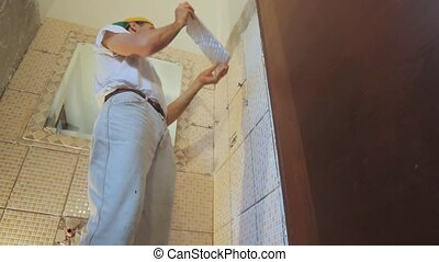 installing tiles - man installing tiles in a bathroom