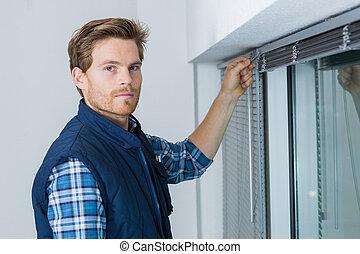 Man installing venitian blinds