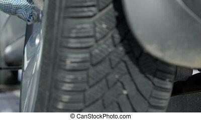 Man installing winter wheel tire on his car