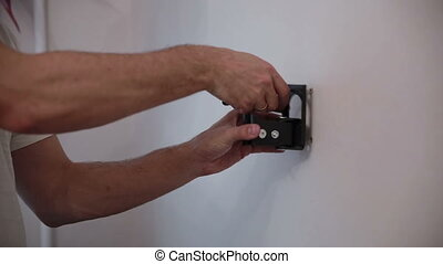 Man installs the holder bracket  on the wall