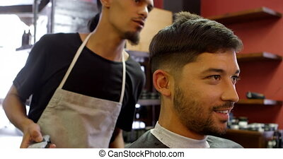 Man interacting with barber while trimming his hair 4k