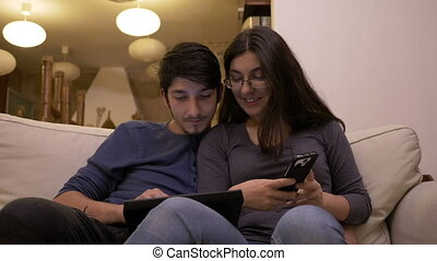 Man introducing data on tablet pc while the woman uses smartphone to dictate data using technology an home