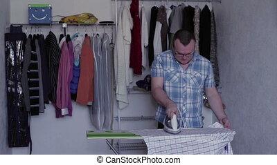 Man iron to iron a man's shirt on the ironing