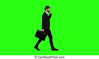 Man is a diplomat, a telephone rings to him and he talks. Green screen. Slow motion