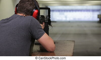 Man is aiming a gun in the shooting-range in shooting gallery