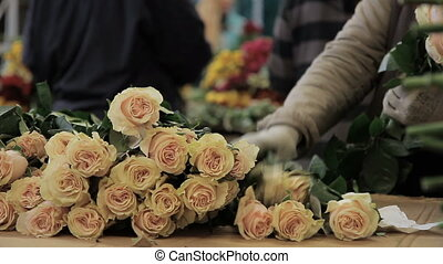 Man is arranging roses into a bunch on streen market.