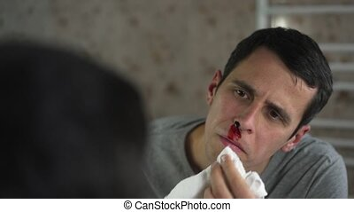 Man wipes blood from a nose with a tissue