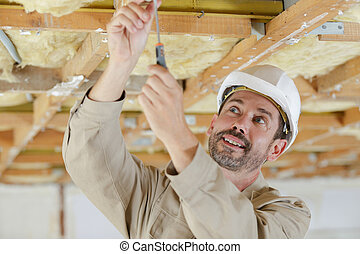 man is building a wooden house structure