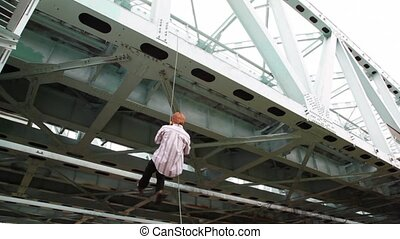 man is chin up on cord suspended to iron bridge with help...
