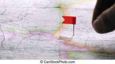 Man is choosing a place for trip putting red flag pin on a map randomly.