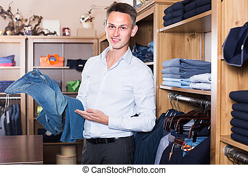 Man is choosing on new jeans