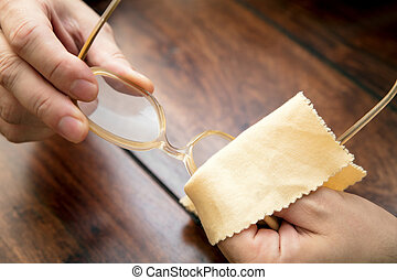 Man is cleaning eye glasses with a microfibre cloth, hornrims