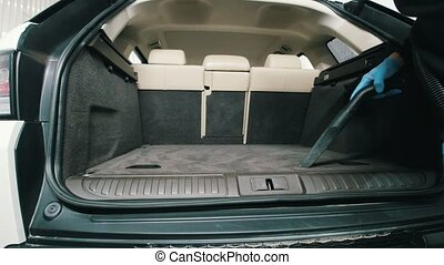 Man is cleaning wardrobe trunk of luxury vehicle with a vacuum cleaner - car detailing