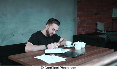 Man is counting up his expenses at the table