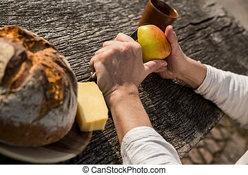 man is cutting a apple in the nature
