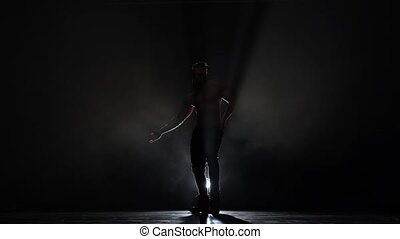 Man is dancing a strip . Black background. Silhouette - Man...