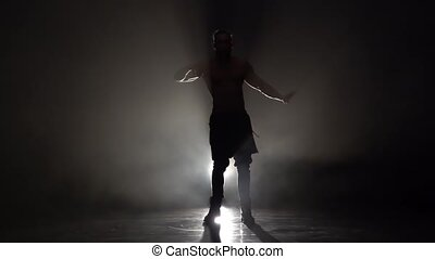 Man is dancing a strip . Black background. Silhouette. Slow motion