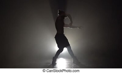Man is dancing a strip . Black background. Slow motion - Man...