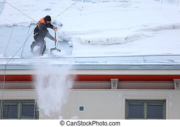 Man is de-icing a snowy Roof - a man secured with ropes is...
