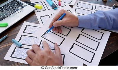 Man is designing a ux user experience design for mobile app for a startup.