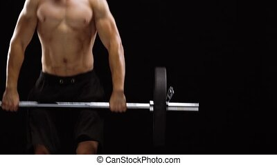 Man is doing exercises with a barbell, is engaged in a crossfit on a black background in the studio