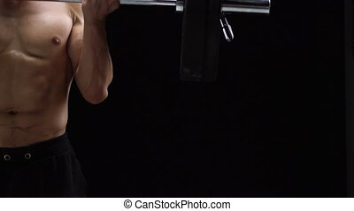 Man is doing exercises with a barbell, training on a black background in the studio