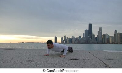 Man is doing push ups on the ebankment. Athlete training outdoors. Downtown with skyscrapers on the background.