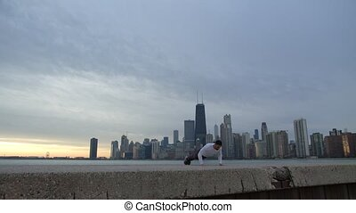 Man is doing push ups on the ebankment. Athlete training outdoors. Downtown with skyscrapers on the background. Seaside sunrise.